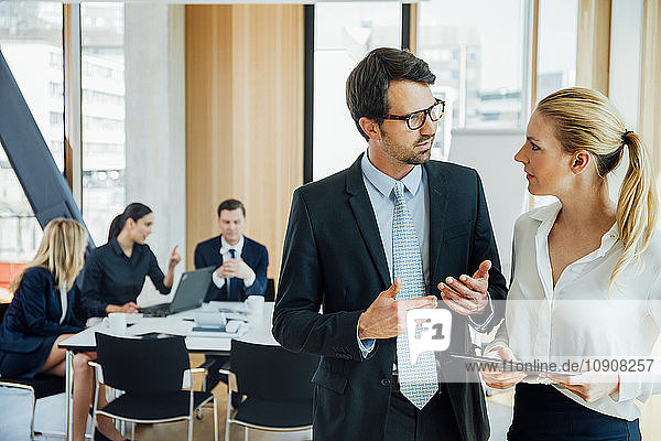 Businessman and businesswoman talking in office with meeting in background