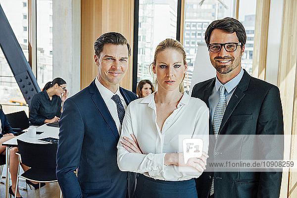 Confident businesspeople in office with meeting in background