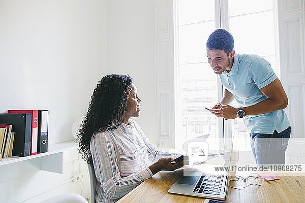 Young businessman and woman working together in office
