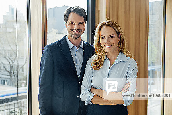 Portrait of confident businessman and businesswoman in office