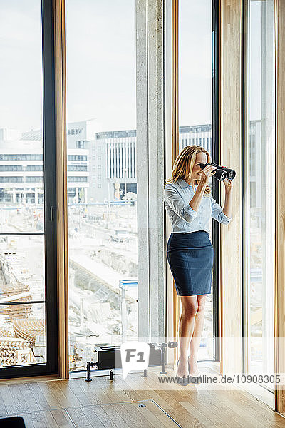 Businesswoman with binoculars looking out of window