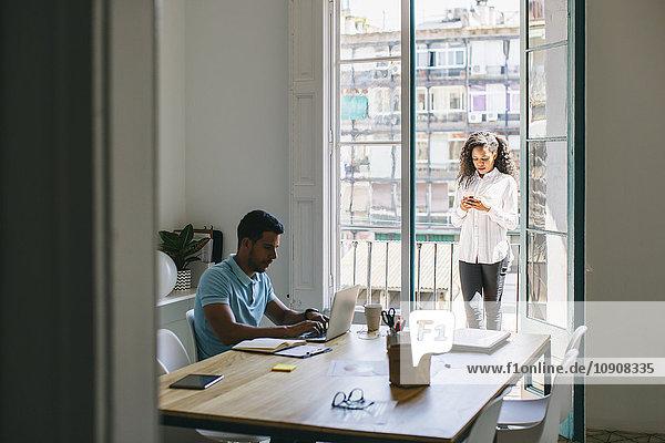 Jungunternehmer und Frau arbeiten zusammen im Amt