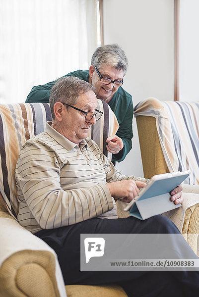Seniorenpaar zu Hause mit digitalem Tablett