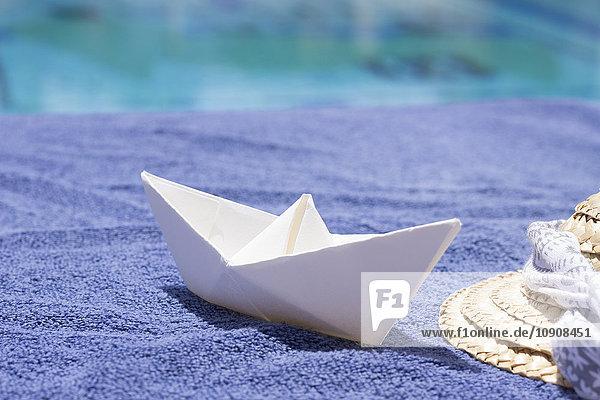 Kleines Papierboot und Strohhut auf Handtuch