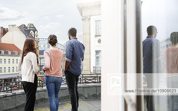 Man and two women standing on roof terrace