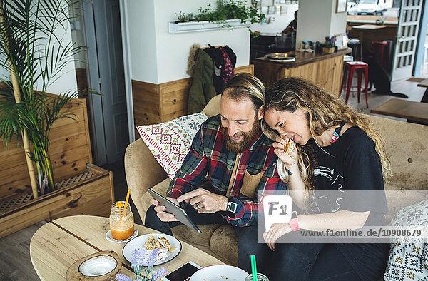 Paar beim Frühstück im Cafe  Blick auf Tablet PC