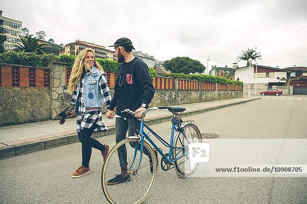 Paar mit Fahrrad und Skateboard zu Fuß auf der Straße