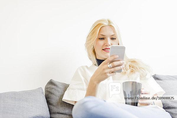 Blonde junge Frau sitzt auf der Couch mit einer Tasse Kaffee und schaut auf das Smartphone.