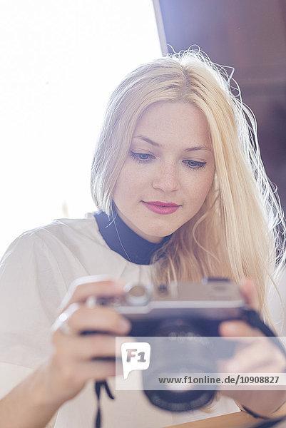 Porträt einer blonden Frau mit Digitalkamera