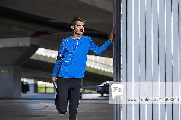 Young sporty man stretching  smartwatch and headphones