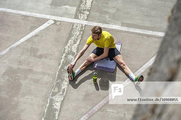 Junger sportlicher Mann  der sich auf dem Betonboden ausstreckt