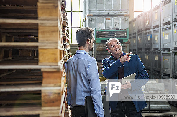 Manager talking to colleague between pallets