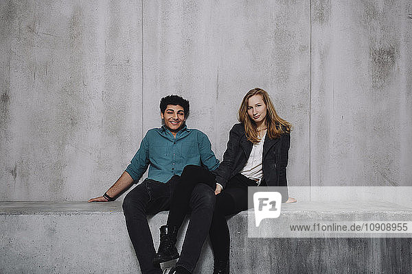 Young couple sitting in front of concrete wall  smiling