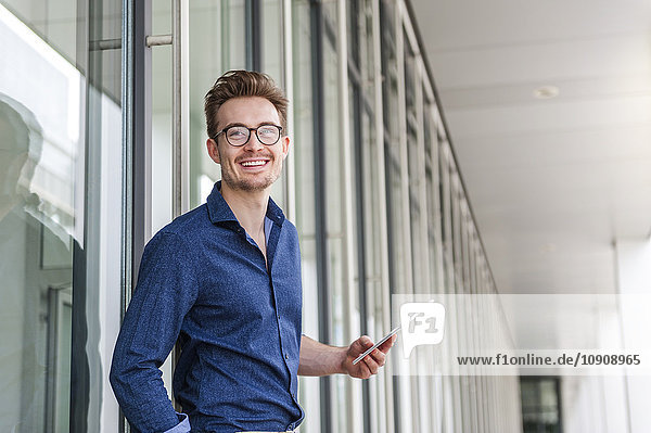 Portrait of young businessman with digital tablet in front of an office building