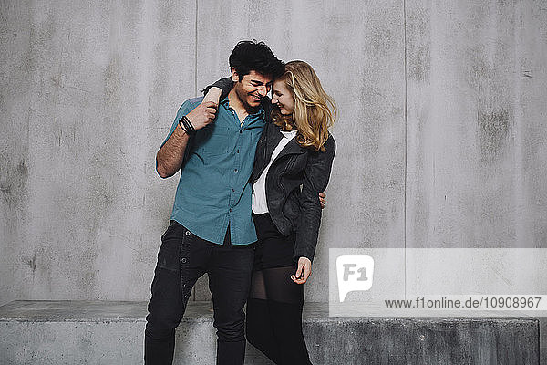 Young couple embracing in front of concrete wall