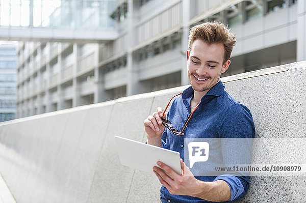 Portrait of young businessman leaning against wall looking at digital tablet