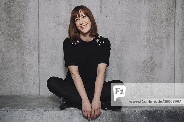 Frau lächelnd  auf Betonwand sitzend