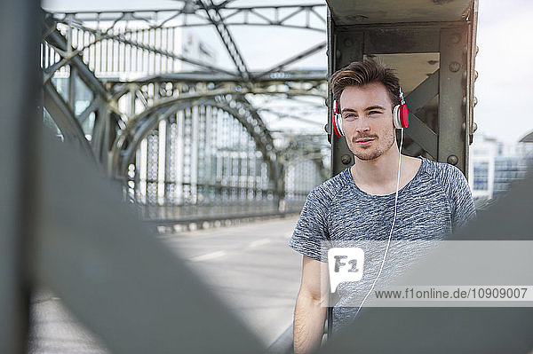 Portrait of young man on a bridge listening music with headphones
