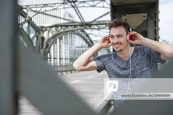 Portrait of smiling young man on a bridge listening with headphones