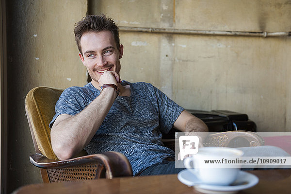Portrait of happy young man sitting in a coffee shop