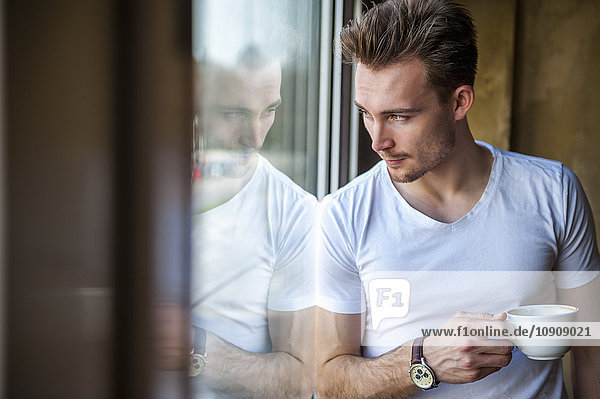 Young man with cup of coffee looking through the window