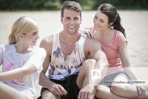 Drei Freunde sitzen am Strand und amüsieren sich.