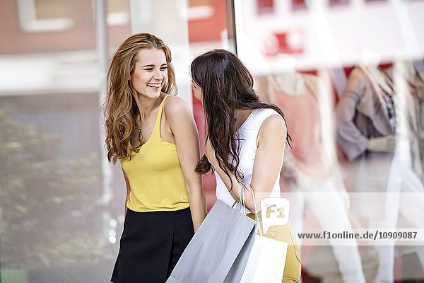 Two happy young women with shopping bags at shop window