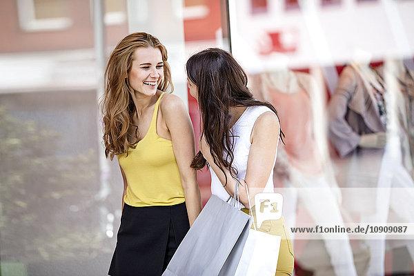 Zwei glückliche junge Frauen mit Einkaufstaschen am Schaufenster