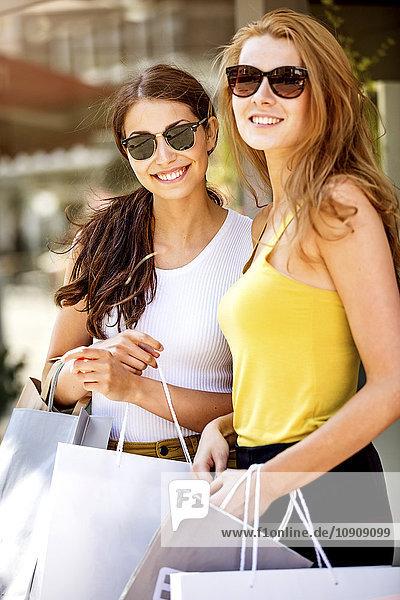 Zwei lächelnde junge Frauen mit Einkaufstaschen