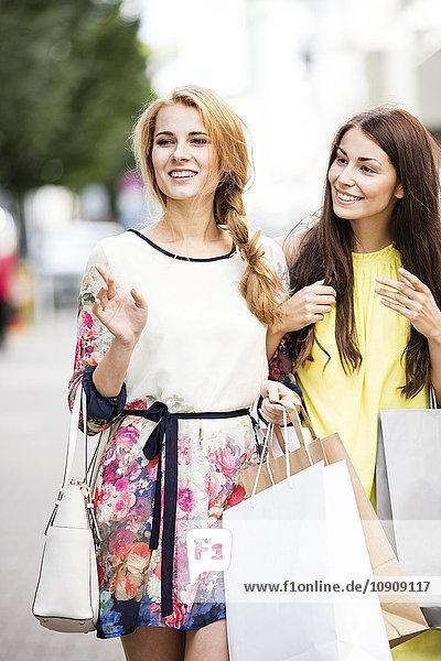 Two smiling young women carrying shopping bags