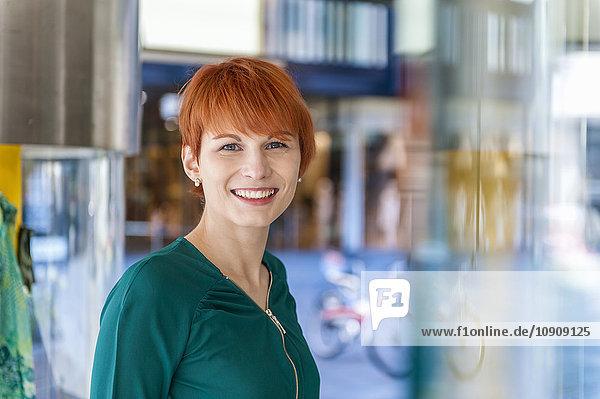 Porträt einer lächelnden jungen Frau am Schaufenster