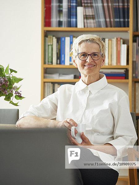 Porträt der lächelnden Seniorin bei einer Tasse Kaffee zu Hause