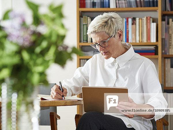 Seniorin mit digitalem Tablett  das etwas aufschreibt.