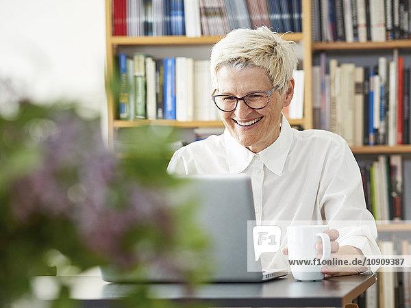 Porträt der lachenden Seniorin mit dem digitalen Tablett zu Hause