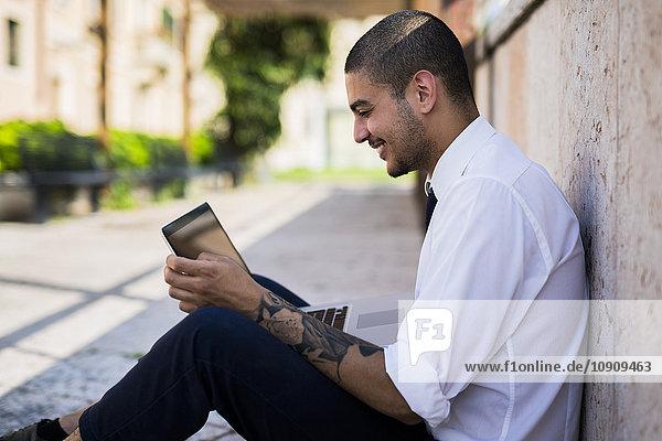 Lächelnder junger Geschäftsmann sitzt auf dem Boden und schaut auf seine Tafel.