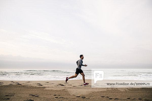 Junger Mann  der am Strand rennt.