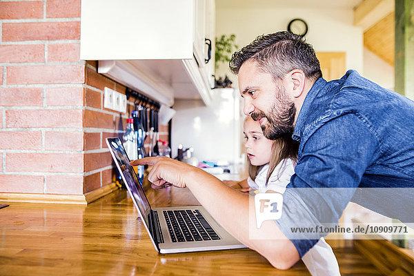 Vater und Tochter mit dem Laptop zu Hause