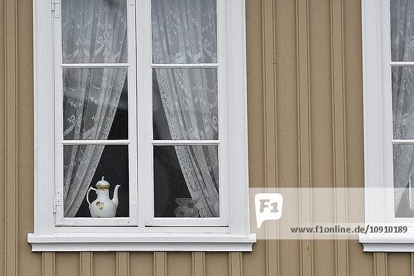 Altmodische Kaffeekanne hinter der Fensterscheibe eines Einfamilienhauses