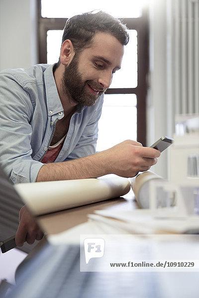 Kreativprofi am Schreibtisch mit Blick aufs Handy