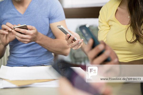 Kollegen mit Smartphones im Büro