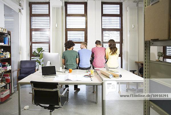 Team von Kreativprofis sitzt auf dem Schreibtisch im Büro