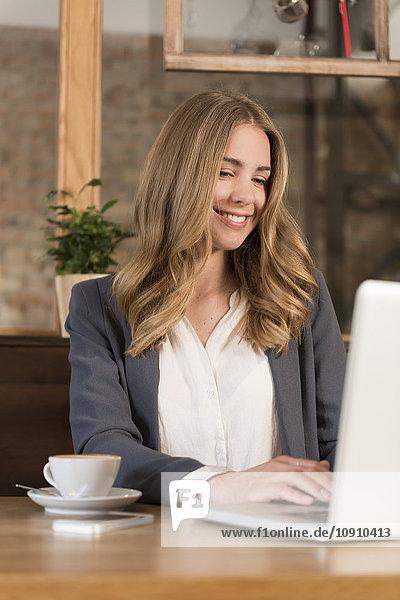 Porträt einer lächelnden jungen Frau mit Laptop im Coffee-Shop
