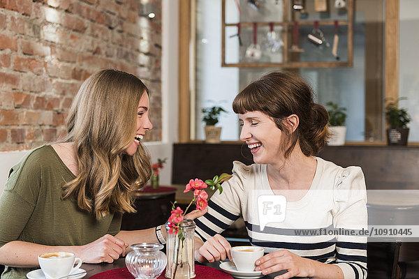 Two best friends sitting in a coffee shop having fun