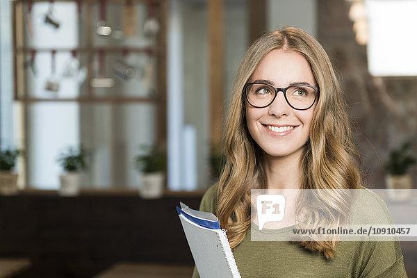 Porträt einer lächelnden blonden Frau mit Notizbuch im Coffee-Shop