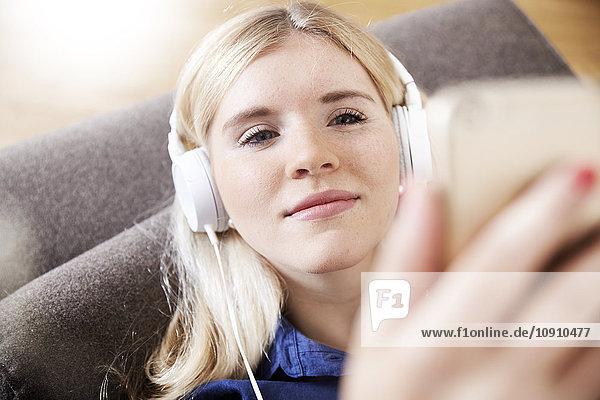 Portrait einer jungen Frau beim Musikhören mit Kopfhörern