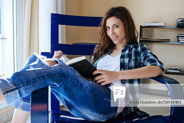 Porträt einer lächelnden jungen Frau mit Buch auf einem Sessel sitzend