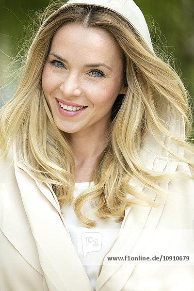 Porträt einer lächelnden blonden Frau in Kapuzenjacke