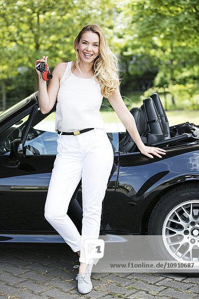 Porträt einer lächelnden blonden Frau mit Autoschlüsseln vor schwarzem Sportwagen