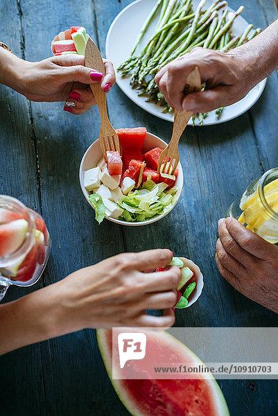 Nahaufnahme der Hände beim Essen von Salat  Wassermelone  Limonade  Spargel und Süßigkeiten