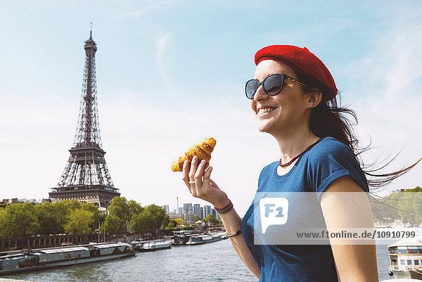 Frankreich  Paris  Frau mit Croissant vor der Seine und Eiffelturm